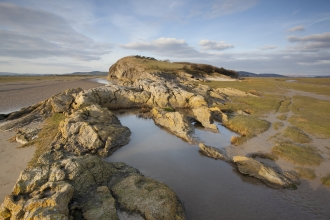 image of Limestone outcrop on edge of saltmarsh and mudflats at Humphrey Head onMorecambe Bay in Cumbria