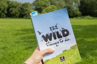 152 Wild Things To Do book cover being held up with natural background