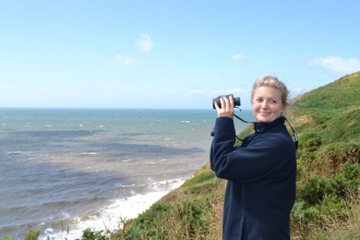 Image of Emily Baxter sea watching with binoculars at St Bees