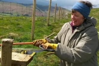 Volunteer fixing a boundary fence