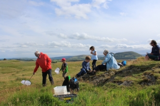 A family uses nets to sweep for insects at Eycott Hill Nature Reserve