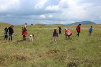 image of people exploring the wetland at eycott hill with dog on lead
