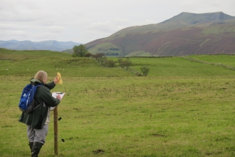 Artist at Eycott Hill Nature Reserve sketching and using viewfinders to frame Blencathra fell