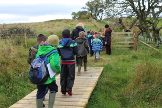 School children crossing bridge at Eycott Hill Nature Reserve