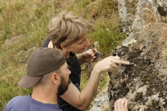 Couple taking a closer look at lichen on rock at Eycott Hill Nature Reserve