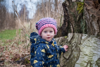 Poppy the toddler stands next to a tree stump