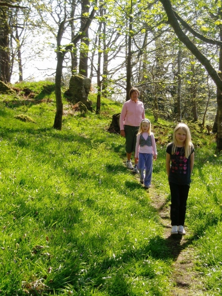 Family walking down path in Craggy Wood near Staveley