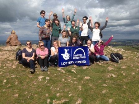 image of people on top of a hill holding Heritage lottery fund banner - Wild paths -copyright dorset wildlife trust