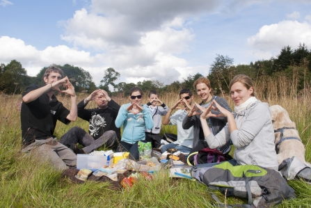 Group of people having a picnic outdoors making a heart shape with their hands - Katrina Martin 2020VISION
