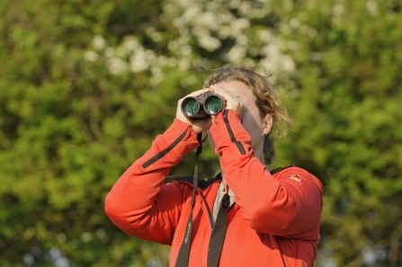 A woman in red top looking through binoculars outside in nature - copyright Terry Whittaker 2020VISION