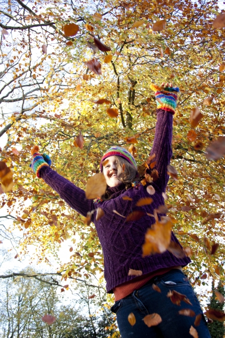 Woman playing in autumn leaves in cozy jumper - copyright Tom Marshall