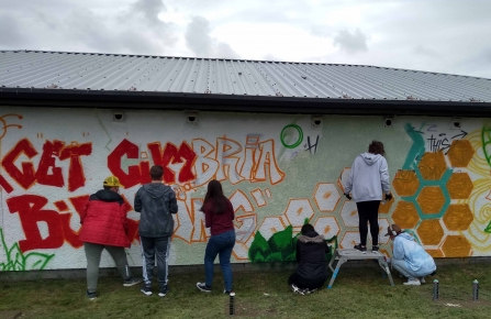 Image of young people painting Get Cumbria Buzzing mural, Salterbeck