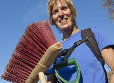 Image of Woman volunteer holding conservation tools and broom