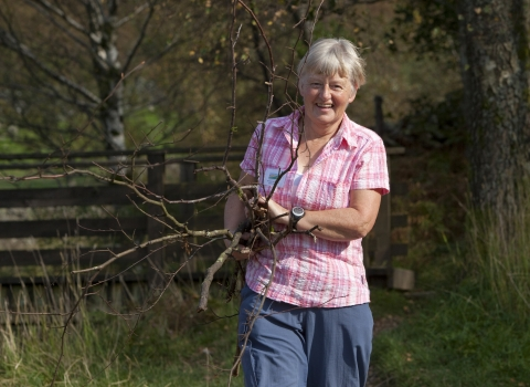 Image of a woman volunteer smiling and holding sticks outdoors