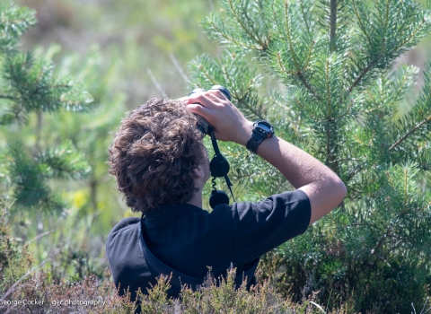 image of young conservationist, Andy Macaulay using binoculars out in the field